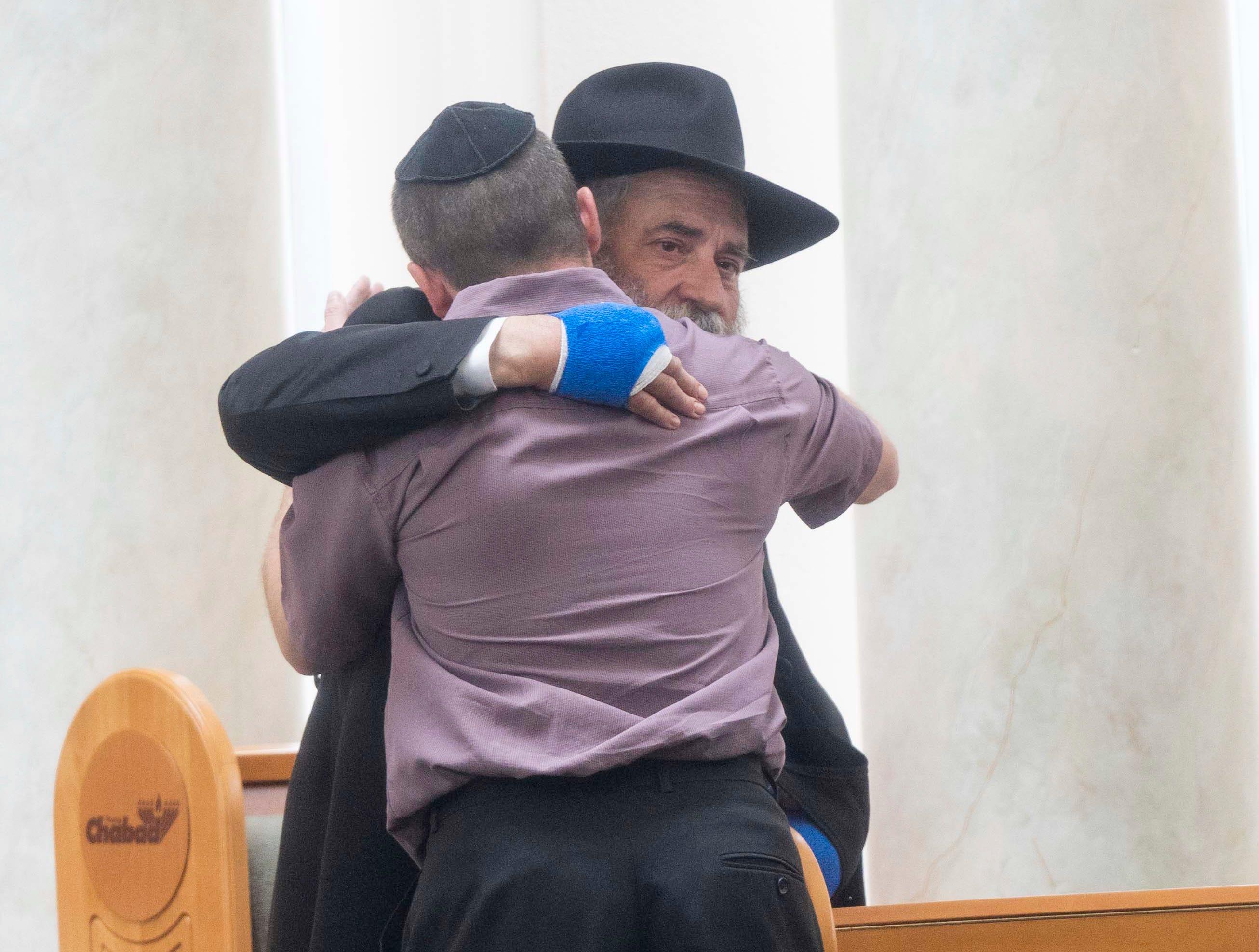 Rabbi Yisroel Goldstein of Chabad of Poway Synagogue gives hugs to family and friends during Lori Gilbert-Kaye's funeral.