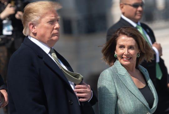 In this file photo taken on March 14, 2019 US President Donald Trump walks alongside Speaker of the House Nancy Pelosi.