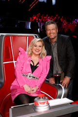 """The Voice"" coaches Kelly Clarkson, left, and Blake Shelton pose with another one of the show's stars, the iconic red, spinning chair."