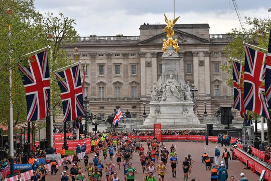 Runners pass Buckingham Palace as they near the finish line in the 2019 London Marathon on April 28, 2019.