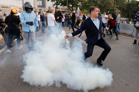 An opponent to Venezuela's President Nicolas Maduro returns a tear gas canister to soldiers who launched it at a small group of civilians and rebel troops gathered outside La Carlota air base in Caracas, Venezuela, Tuesday, April 30, 2019. Venezuelan opposition leader Juan Guaidó took to the streets with activist Leopoldo Lopez and a small contingent of heavily armed troops early Tuesday in a bold and risky call for the military to rise up and oust socialist leader Nicolas Maduro. (AP Photo/Ariana Cubillos)