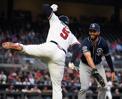 April 29: The Atlanta Braves' Freddie Freeman attempts to avoid the tag of San Diego Padres first baseman Eric Hosmer during the third inning at SunTrust Park. The Braves won the game, 3-1.