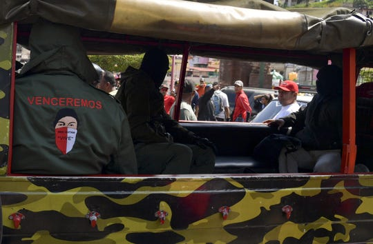 """Masked members of a """"colectivo,"""" pro-government cells, attend a rally in Caracas on January 7, 2019. - """"Colectivo"""" members are referred to as both, revolutionary idealists and thugs."""