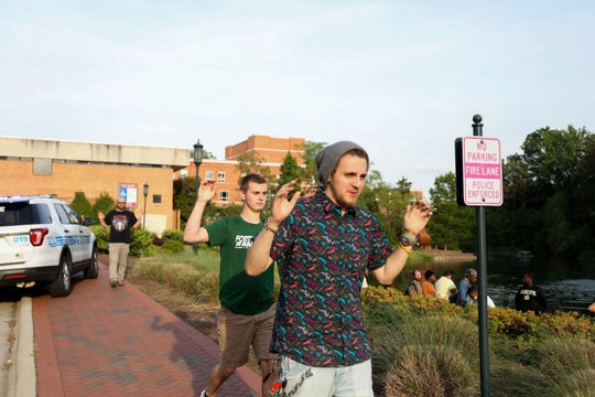 Students and faculty file out of buildings with their hands up during a lockdown after a shooting on the campus of University of North Carolina Charlotte in University City, Charlotte, on April 30, 2019.