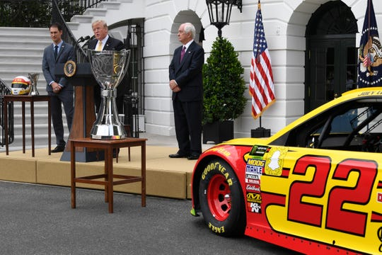President Donald Trump at Tuesday's NASCAR event, along with champion driver Joey Logano and team owner Roger Penske.
