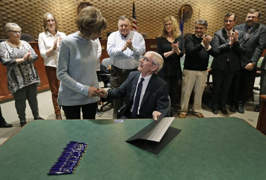 Gov. Tony Evers shares a moment with Sandy Ellis after he signed a bill naming the Interstate 41-U.S.10/State 441 interchange after the late state legislator Mike Ellis at Neenah City Hall. Sandy is the widow of Ellis. The two are surrounded by family, friends and officials.
