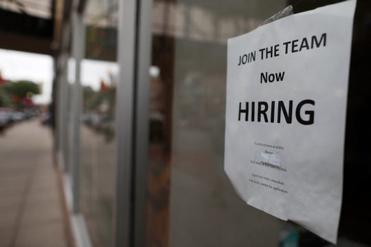 "In this 2018 file photo a ""now hiring"" sign hangs in the window of a Chinese restaurant in downtown Fargo, N.D. Small business hiring is slowing, according to numbers released by payroll provider ADP."