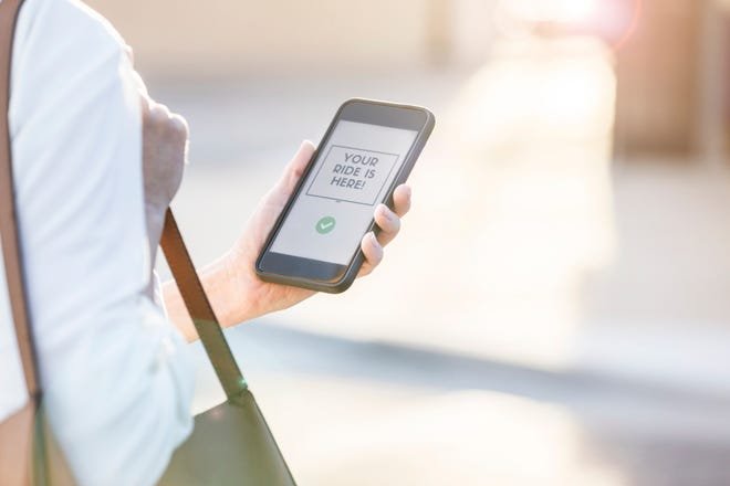 Confident businesswoman uses ride share app on her smart phone. The message on the phone indicates that her ride has arrived.