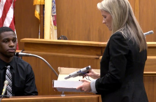 Emily Cartmell, assistant Monmouth County prosecutor, displays the weapon that Dante Allen aledgedly used to shoot at  Asbury Park police Officer Terrance McGhee during a foot chase.  Allen is on trial in State Superior Court in Freehold Wednesday, May 1, 2019,  charged with the attempted murder of the officer.