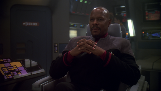 "Avery Brooks as Captain Benjamin Sisko sits on the bridge of the Defiant in a scene from ""Star Trek: Deep Space Nine."""