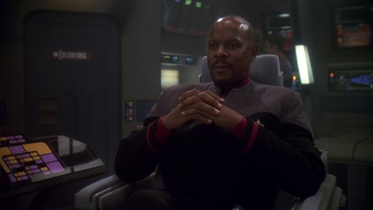 "Avery Brooks as Captain Benjamin Sisko sits on the bridge of the Defiant in a scene from ""Star Trek: Deep Space Nine."""