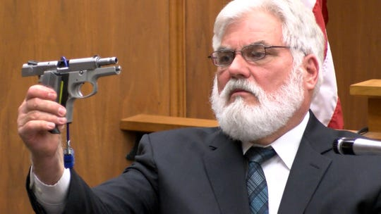 Randolph Toth, an investigator with the New Jersey State Police, holds the weapon that Dante Allen is charged with using to shoot at Asbury Park police Officer Terrance McGhee.  Allen is charged with attempted murder trial during his trial in State Superior Court in Freehold Tuesday, April 30, 2019.