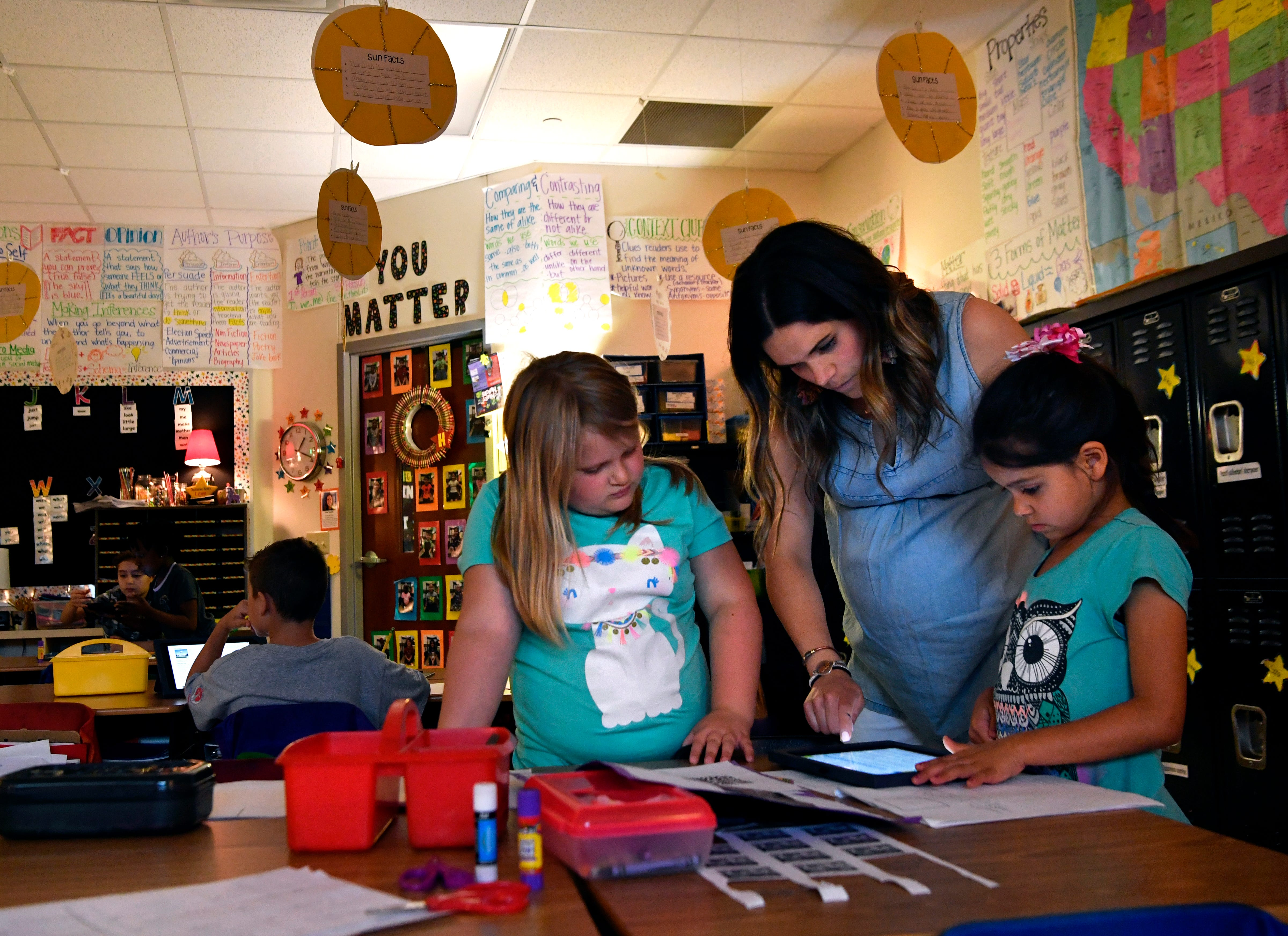 Molly Harless assists Hailey Shaw (left) and Layla Mangum during Harless' second-grade class at Lee Elementary School on Wednesday.