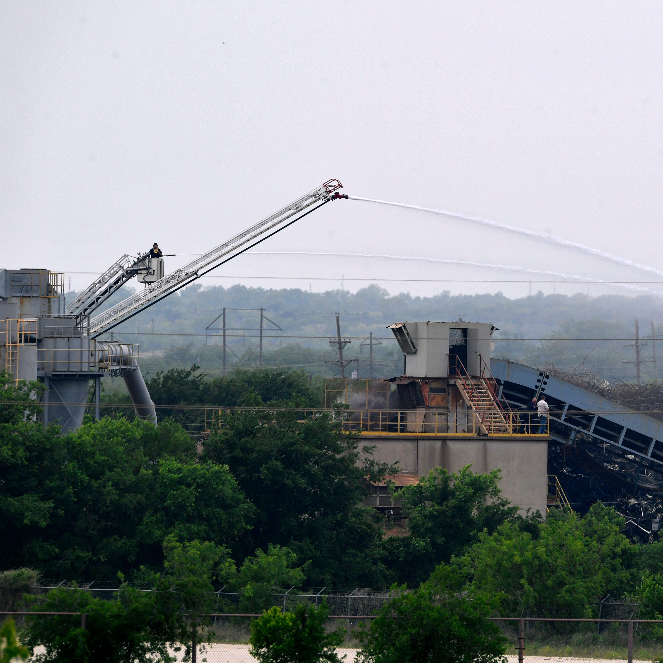 Abilene salvage yard debris still smoldering Wednesday after fire