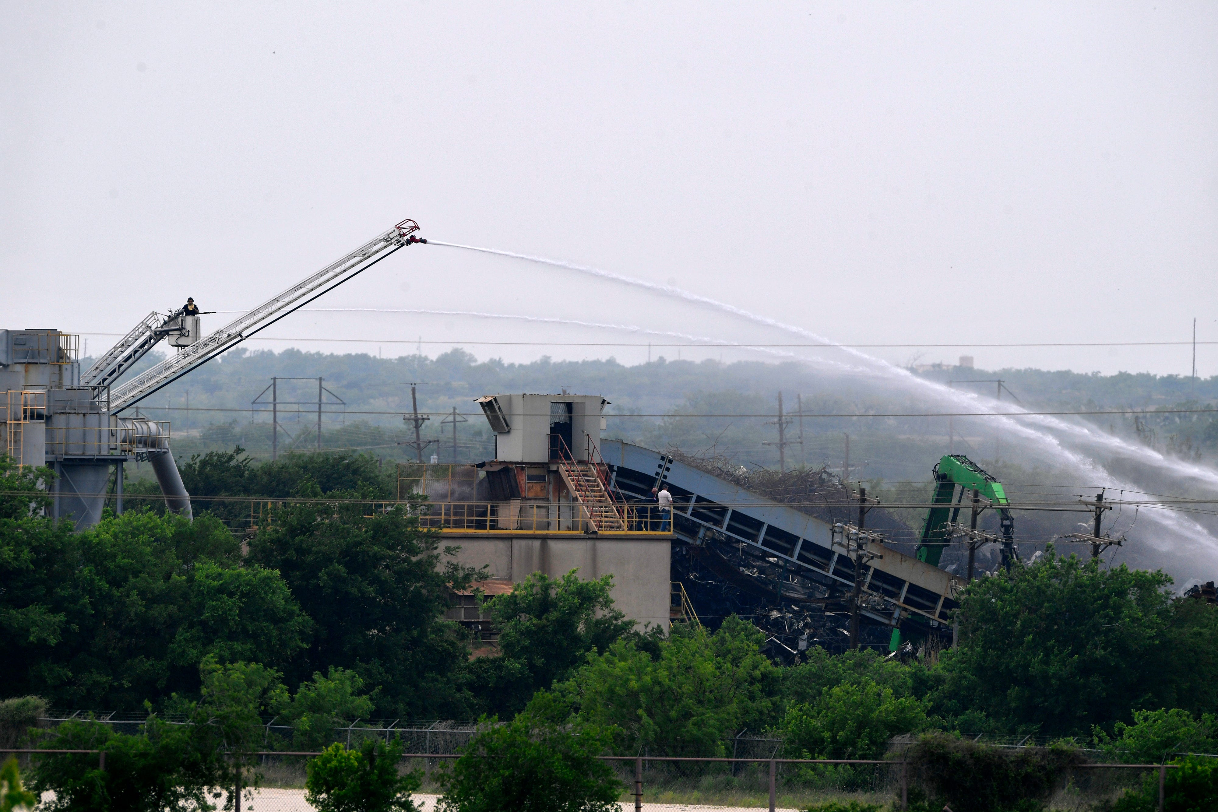 Abilene Fire Department crews spray water on a scrap pile at Pine Street Salvage mid-morning Wednesday. Crews initially arrived on the scene just after 1 a.m.