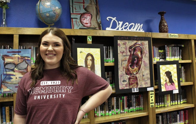 """Hawley High School senior Sally Stokes never dreamed she'd get almost $88,000 in scholarships for her college education. Behind her are examples of her art, including """"Tagged"""" (below the Dream sign)."""
