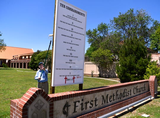 Bill Alexander on April 25 rolls white paint on the back of a sign bearing the Ten Commandments at First United Methodist Church.