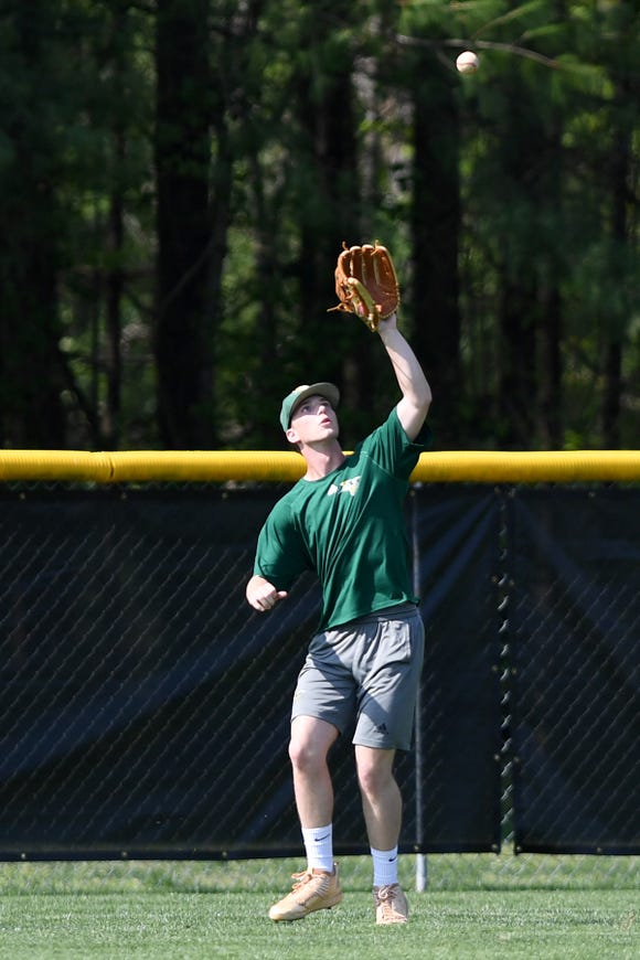 Christ School's Mickey Meguiar catches a ball in the outfield as he practices with the team on April 29, 2019.