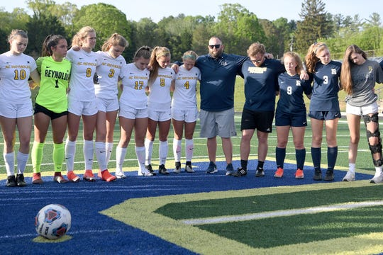 Roberson girls soccer coach Josh Martin brings together rival teams from Roberson and Reynolds before their game for a moment of silence to honor UNC Charlotte shooting victim Riley Howell before their game on May 1, 2019. Howell was a graduate of Roberson High School and a member of the soccer team. Police say that Howell's actions taken during the shooting saved lives.