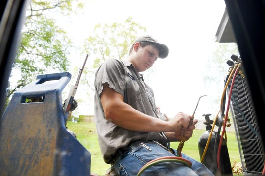 Tyler Roberts, an apprentice with Gentry Heating, Inc., works to change out an old furnace for a heat pump at a house in Canton on April 30, 2019. Roberts was working with an HVAC mechanic on the job.
