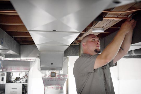 Spencer Hollifield, an HVAC mechanic with Gentry Heating, Inc., works to change out an old furnace for a heat pump at a house in Canton on April 30, 2019. Hollifield has been with the company for three years after going to school for the trade for a year.