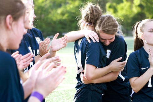 Roberson's Isabelle Ingle, left, is comforted by teammate Julia Bankard as the team gets ready to play after a moment of silence to honor UNC Charlotte shooting victim Riley Howell before their game on May 1, 2019. Howell was a graduate of Roberson High School and a member of the soccer team. Police say that Howell's actions taken during the shooting saved lives.