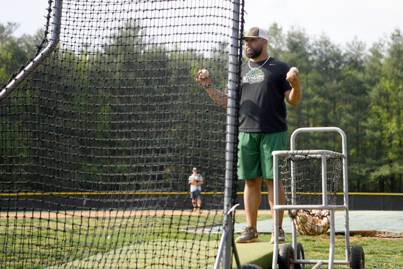 Christ School coach Cody Geyer pitches to his players from behind a screen during practice on April 29, 2019.