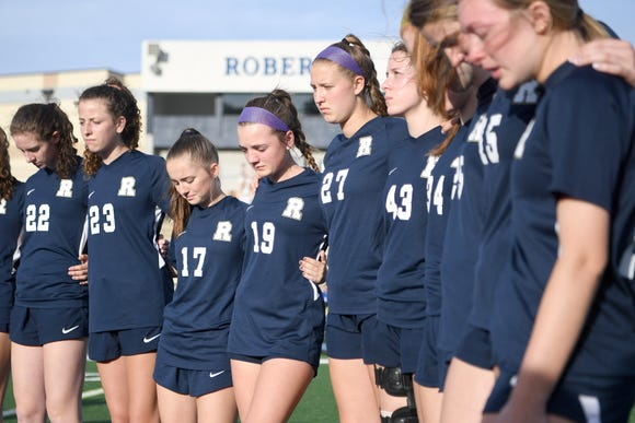 Roberson varsity girls soccer players observe a moment of silence to honor UNC Charlotte shooting victim Riley Howell before their game on May 1, 2019. Howell was a graduate of Roberson High School and a member of the soccer team. Police say that Howell's actions taken during the shooting saved lives.
