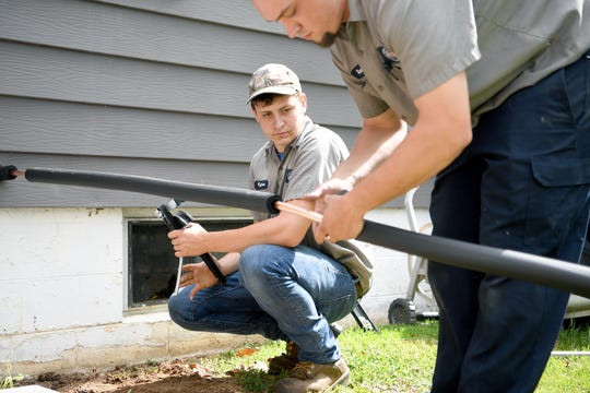 Tyler Roberts, an apprentice, watches as Spencer Hollifield, an HVAC mechanic with Gentry Heating, Inc., works with him to change out a furnace for a heat pump at a house in Canton on April 30, 2019.