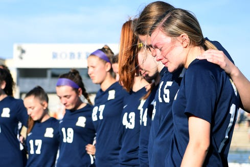 Roberson's Julia Bankard and Nola Goosmann, right, comfort one another during a moment of silence to honor UNC Charlotte shooting victim Riley Howell before their game on May 1, 2019. Howell was a graduate of Roberson High School and a member of the soccer team. Police say that Howell's actions taken during the shooting saved lives.
