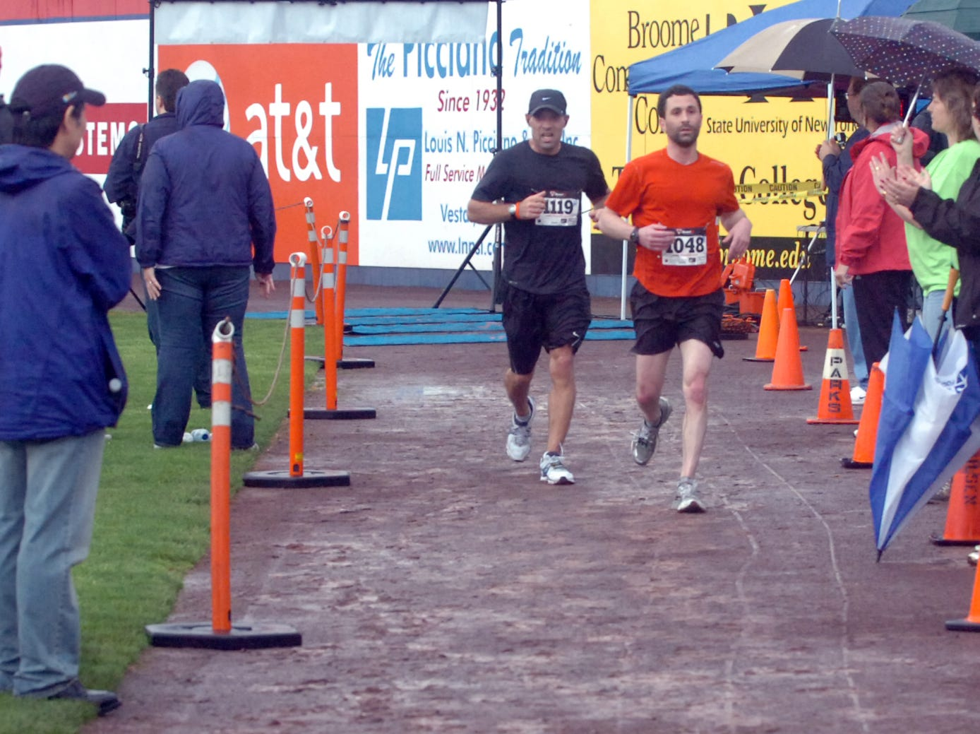 2011: Frank Prusick, left, and John Murray cross the finish line of the Greater Binghamton Bridge Run Half Marathon on Sunday. Roughly 890 runners competed in the inaugural race on a course through streets and over bridges in downtown Binghamton.