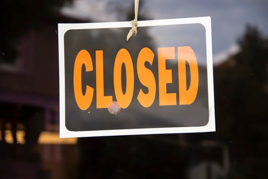 Closed sign hanging in business window
