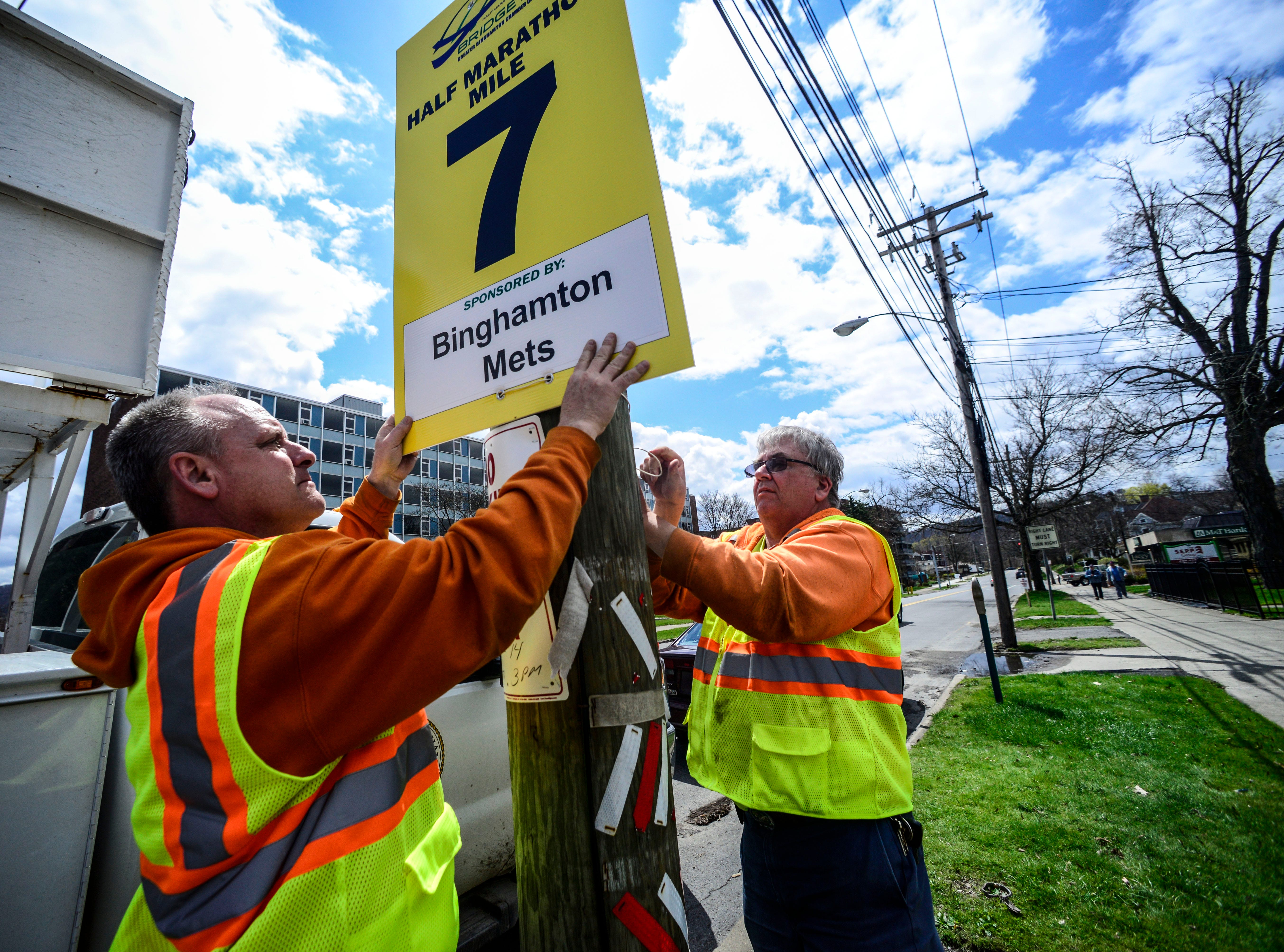 2014: Traffic sign maintainers Rich Fiato, Binghamton resident holds the mile marker sign for the Greater Binghamton Bridge Run while Nicholas Carman, Harpursville resident, ties it in on Front Street on Friday.