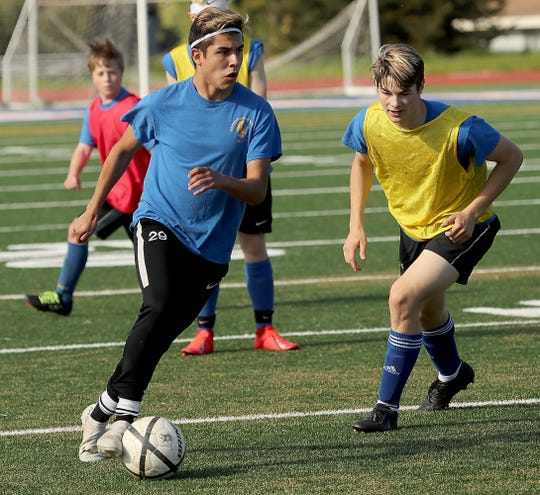 Bremerton's Luis Clemen (left) runs through a drill during practice at Bremerton Memorial Stadium on Tuesday, April 30, 2019.