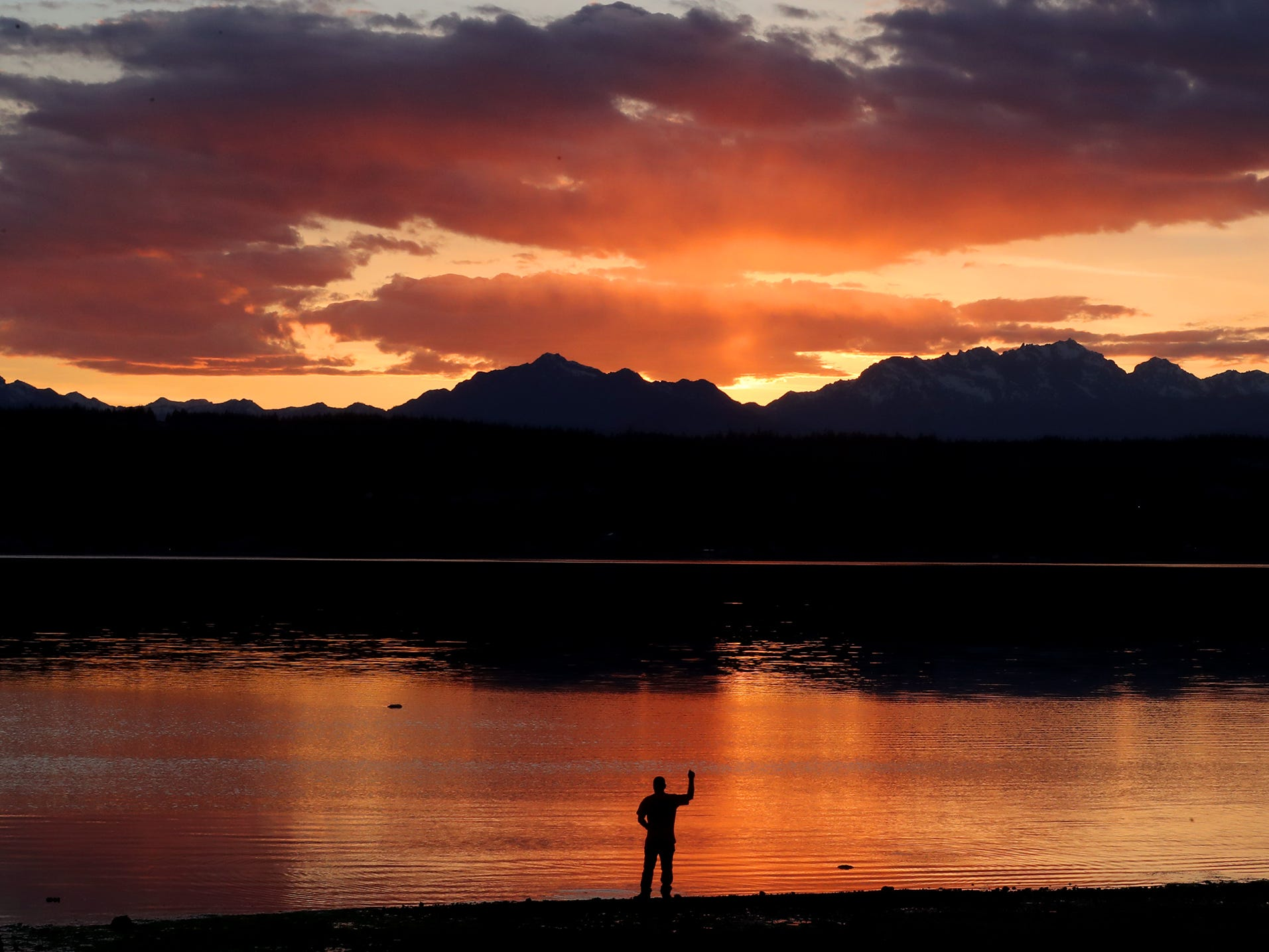 John Bart tosses a rock into the water as he skips stones during sunset at the Tracyton Boat Launch on Tuesday. Temperatures are forecast to reach into the 70s through the weekend.