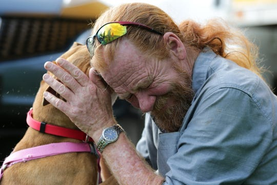 Daisy, a rescue dog, plays with William Coplen, director of All Dogs Come From Heaven Rescue, Tuesday, April 30, 2019, in Amelia, Ohio.
