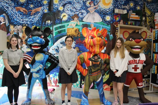 "Trinity Tankersley, Vivian Zhuang and Hannah Willmott of Villa Madonna Academy High School/Junior High painted ""Hero Bearcats"" for the University of Cincinnati's public art campaign."