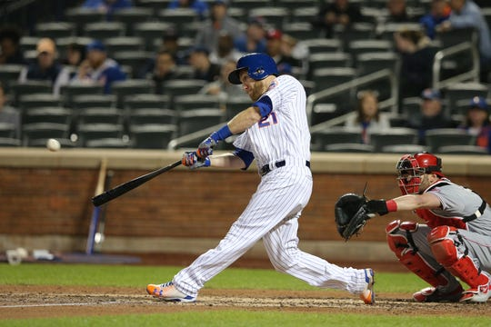 Apr 30, 2019; New York City, NY, USA; New York Mets third baseman Todd Frazier (21) hits a solo home run against the Cincinnati Reds during the seventh inning at Citi Field. Mandatory Credit: Brad Penner-USA TODAY Sports