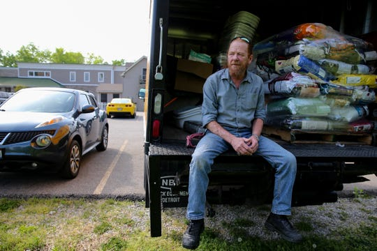 William Coplen, Director of All Dogs Come From Heaven Rescue, is pictured sitting on the back of a truck full of supplies, Tuesday, April 30, 2019, at All Dogs Come From Heaven Rescue in Amelia, Ohio.