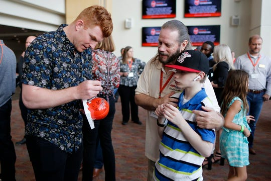 Bengals quarterback Andy Dalton signs an autograph for Parker Kahle and his dad David Kahle of Milford during the Legends Past and Present event benefitting the Andy and JJ Dalton Foundation and Ken Anderson Alliance at Paul Brown Stadium in downtown Cincinnati on Tuesday, April 30, 2019.