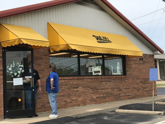 A customer being told that Whitt's Barbecue has temporarily shut down, as a sign hangs on the door announcing the deaths of the restaurant owners.