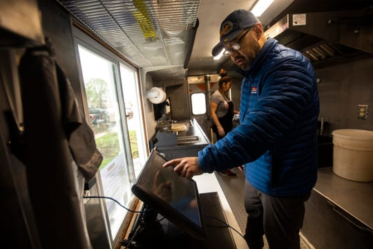 La Flama owner Martin Garcia, right, gets change for a customer while Angelica Nogueda, back, prepares an order after water from the Mississippi River broke through temporary flood barriers, Wednesday, May 1, 2019, in Davenport, Iowa. Flood water has come up around the restaurant location that Garcia operates and is working from one of his food trucks.