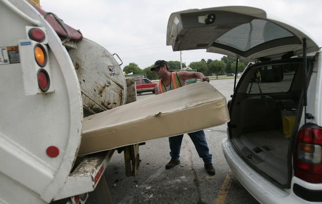 Shawn McFarland helps throw a mattress into a garbage truck during Scrub Day at Hoover High School in Des Moines in 2008.