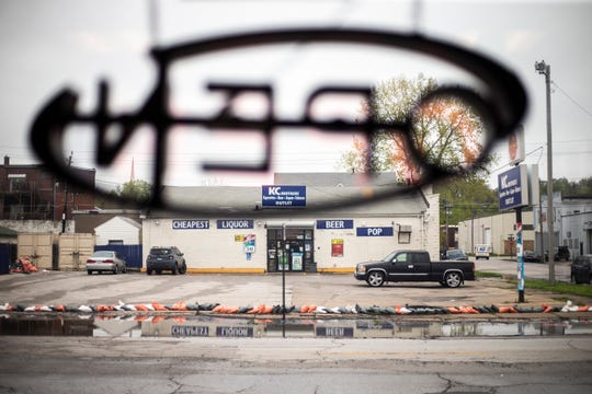 Ramesh KC liquor store is seen past an open sign inside Cinnamon N Sage after water from the Mississippi River broke through temporary flood barriers, Wednesday, May 1, 2019, along 2nd Street in Davenport, Iowa.