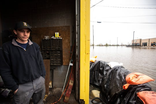 Hubill Power Systems battery technician Seth Klinefelter stands in a garage next to a wall of sandbags where they are pumping water out from the Mississippi River broke through temporary flood barriers, Wednesday, May 1, 2019, in Davenport, Iowa.
