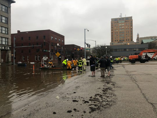 Emergency responders work to rescue people from buildings as floodwaters overtake downtown Davenport near the intersection of Pershing Avenue and East 2nd Street on Tuesday, April 30, 2019, after HESCO barriers holding back the Mississippi River failed.