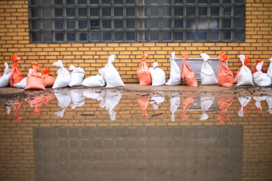 Sandbags are reflected in water in front of Hubill Power Systems after water from the Mississippi River broke through temporary flood barriers, Wednesday, May 1, 2019, along 2nd Street in Davenport, Iowa.
