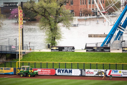 A Quad City River Bandits grounds crew staffer fertilizes a portion of the outfield after water from the Mississippi River broke through temporary flood barriers, Wednesday, May 1, 2019, at Modern Woodman Park in Davenport, Iowa.
