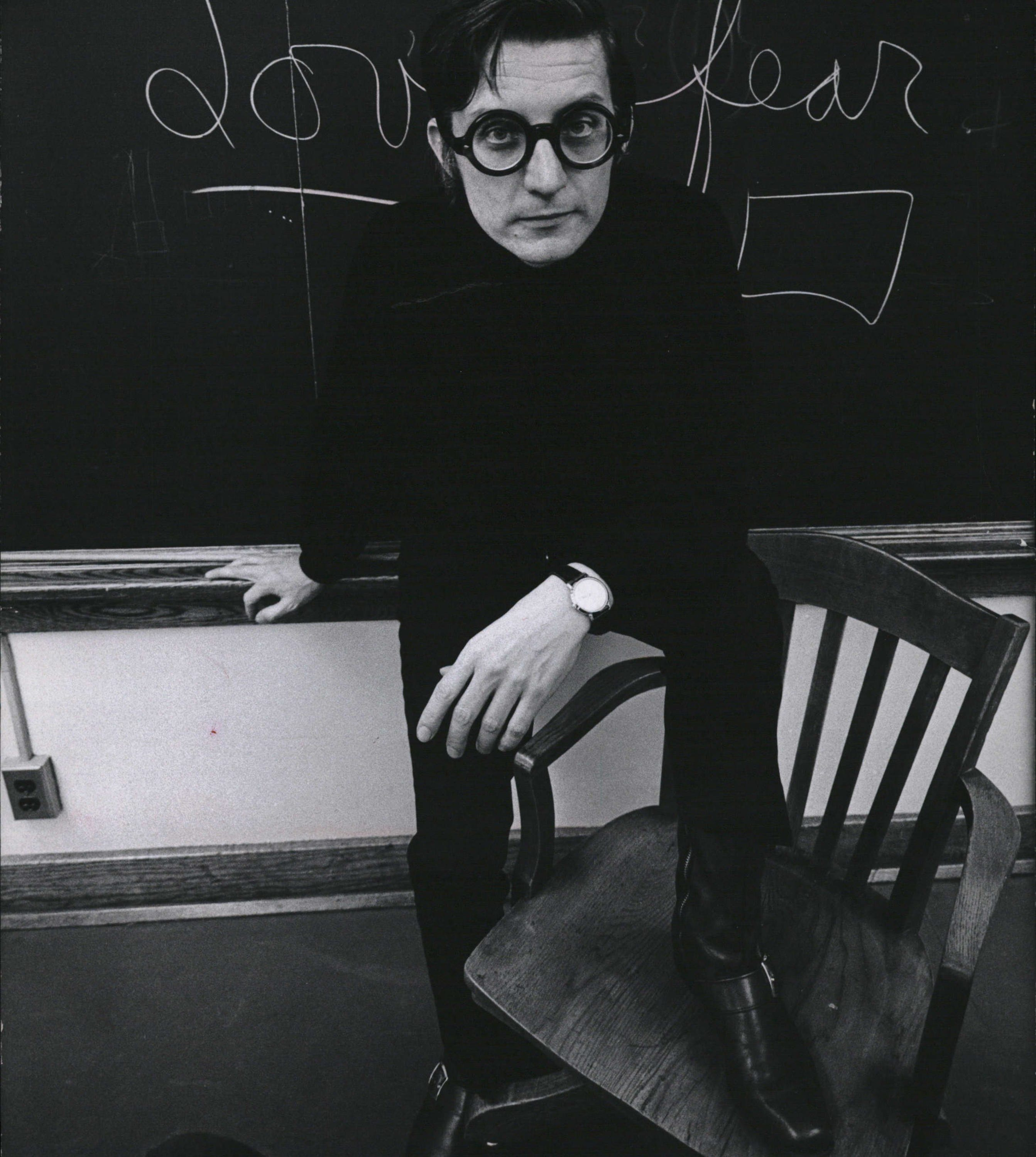 Russ Gibb poses in front of a chalkboard  in 1969.