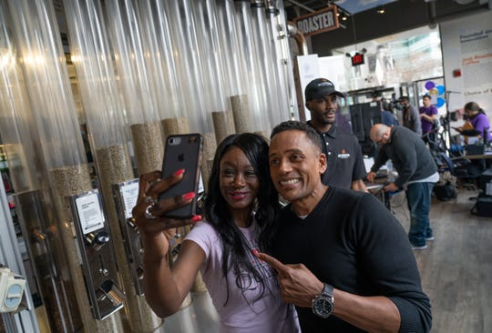 "Shamika Robinson of Detroit takes a selfie with actor Hill Harper as he does promotion about ""Credit over Coffee"" as part of an effort to build credit scores through a new program called Experian Boost at his business the Roasting Plant Coffee in downtown Detroit on Wednesday, May 1, 2019."